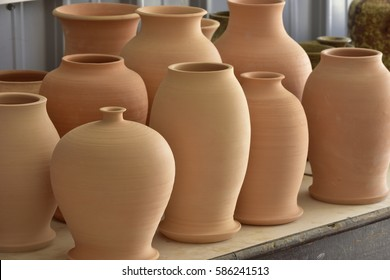 In a pottery factory, many pottery stands on wooden shelves