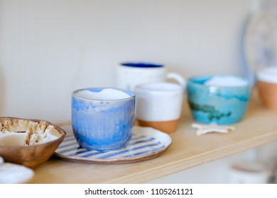 pottery handcraft hobby. assortment of handmade clay plates jugs mugs and cups