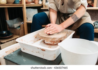 Pottery making art therapy process front view. Picture of female potter who molds some pottery on spinning potters wheel. Art therapy at potters studio