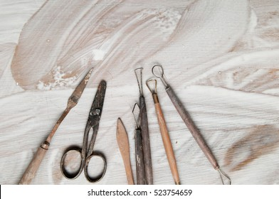 Pottery making tools on a white desk