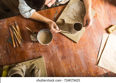 pottery, stoneware, ceramics art concept - workplace of potter, craftsman bent over clay cup with tools, male hands connecting pieces of fireclay, young male sits at a workshop behind table, flat lay