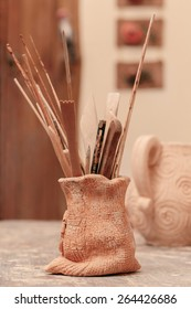 Pottery tools. Still life of the clay pot with pottery tools and brushes