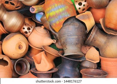 Pottery vessels and other objects made of clay and ceramic materials in a pile with broken earthenware, stoneware and porcelain
