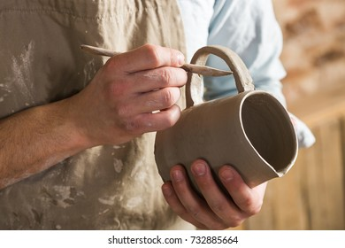pottery, workshop, ceramics art concept - closeup on young ceramist hands with unbaked clay jug, craftsman stand at a workplace, hands holds the clay cup and tools