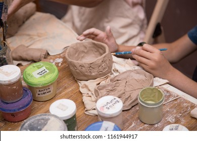 Pottery workshop for kids, raw clay, sculpting tools, glazing and painting clay pots