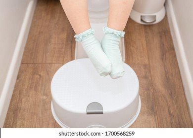 Potty training. Toddler little girl of preschooler age sitting on toilet feet and legs