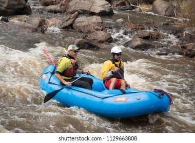 Poudre River, Colorado, USA – 8 May 2018: Two men whitewater rafting on the popular Poudre River in Colorado during spring runoff
