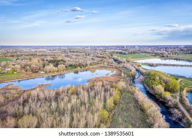 Poudre RIver flowing towards Fort Collins through Colorado foothills, early spring aerial view