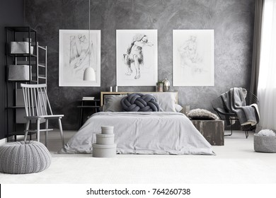 Pouf and boxes near grey chair in monochromatic bedroom with drawings on concrete wall above king-size bed
