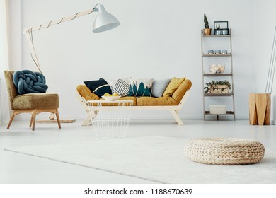 Pouf and chair in white living room interior with lamp next to mustard wooden sofa. Real photo
