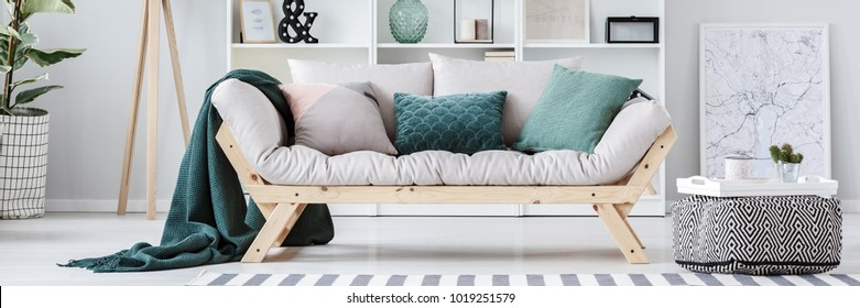 Pouf next to beige sofa with green cushions in apartment interior with map poster