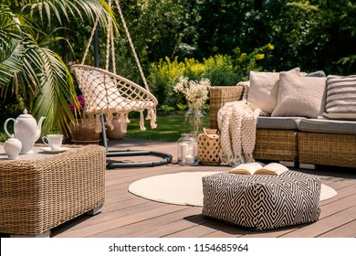 Pouf on wooden terrace with rattan sofa and table in the garden with hanging chair. Real photo