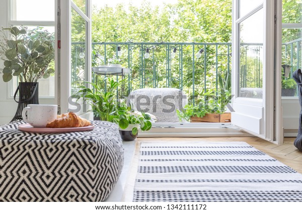 Pouf with pink plate with coffee mug and croissant in blurred foreground in real photo of room with fresh plants, rug on the floor and open door to balcony