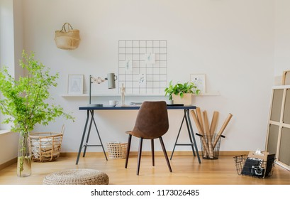 Pouf and plants in white home office interior with brown chair at desk with lamp. Real photo