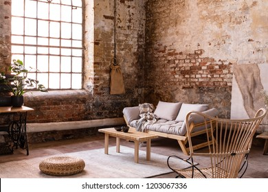 Pouf and wooden table on carpet near window in bright wabi sabi interior with sofa and armchair. Real photo