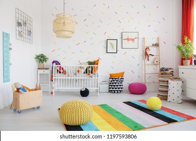 Poufs on colorful rug in scandi baby's bedroom interior with lamp, cradle and posters. Real photo