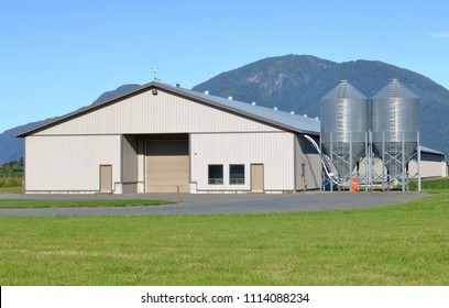 Poultry feed bins and building in a valley with rolling mountains in the background.