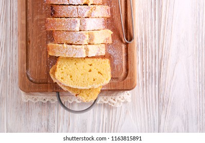 Pound cake, with icing sugar, sliced on wooden board