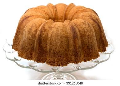 Pound cake on cake plate.  Isolated on white background.