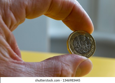 Pound coin held by fingertips
