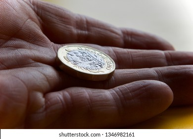 Pound coin in palm of hand close up