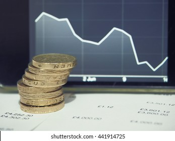 Pound coins on financial figures balance sheet with graph of decreasing exchange rate of the pound sterling. British Pound (GBP) currency after EU referendum result.