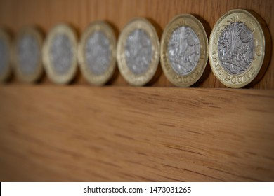 pound coins in a row on a wooden surface