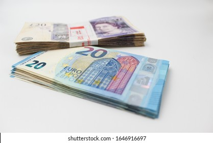 Pounds and Euro banknotes, pile of money. Stacked on top of each other, isolated. 20 eur and 20 £ currency.