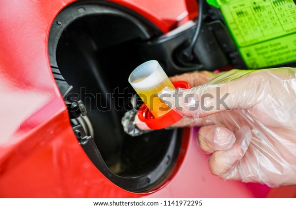 Pour additive liquid into car tank. Maintenance for long use without repair. Additional fluid for gasoline.