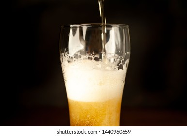 pour beer in a beer glass, tasty fresh beer in a beer grocery glass