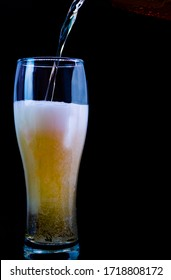 Pour beer into a glass on a black background.Light beer in a glass,draft.Fresh light beer.Close-up.