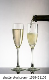 pour champagne in two glasses on a white or black background