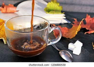 Pour coffee in a autumn setting into a glass cup - a glass cup is standig beside dry and colorful autumn leaves and a book in the background and someone is pouring coffee into it