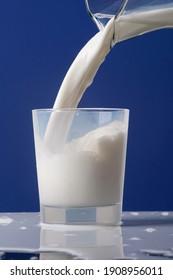 Verser le lait crémeux de la carafe ou le mélanger dans un verre. Le lait se déverse sur la table. Photo isolée sur fond bleu