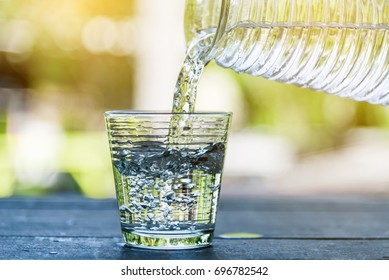 Pour drinking water into the glass. Ice in glass and drinking water. Clean drinking water. Drink healthy water.