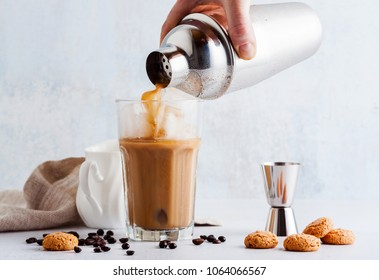 pour the frappe from the shaker into a tall glass , beautiful and clean composition with coffee beans and amaretti biscuits