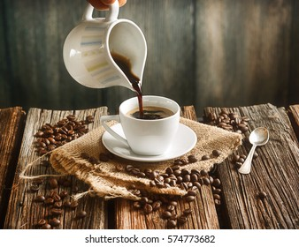 pour the hot coffee in small white cup - coffee beans around