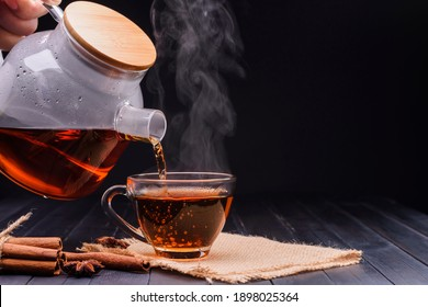 Pour the hot tea into the teacup. A teacup placed on an old wooden table In a black background, there was soft sunlight shining into a warm atmosphere.