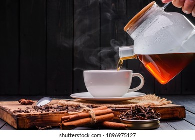 Pour the hot tea into the white teacup. A teacup placed on an old wooden table In a black background, there was soft sunlight shining into a warm atmosphere.
