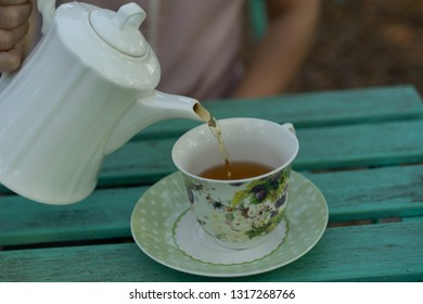Pour hot tea from the kettle