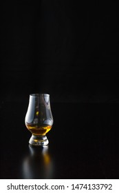 A pour of Kentucky straight boubon whiskey in a glencairn glass in front of a black background. The glass reflection shines off the table. Copy space.