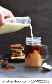 Pour milk into a glass full of coffee against a dark background with nut corners - freshly brewed hot coffee against a dark setting with milk flowing into it