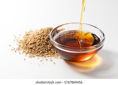 Pour the oil into the sesame oil placed on a white background.