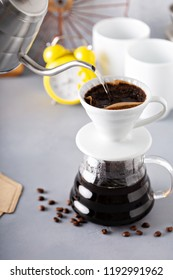 Pour over coffee being made with a kettle and glass carafe with hot water being poured and alarm clock in the background