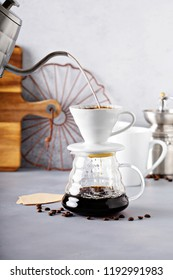 Pour over coffee being made with a kettle and glass carafe with hot water being poured