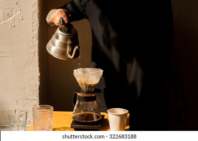 pour over coffee brewing method whole process by barista girl with tattoos cool shadows natural light background