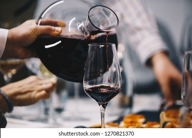 Pour red wine from the decanter into the glass.