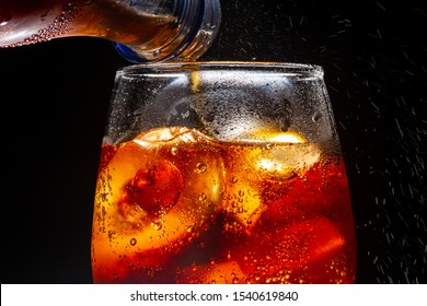 Pour soft drink in glass with ice splash on dark background,Castillo De Coca, Soda, Cola, Pouring, CarbonatedมSoft drink being poured into glassมSoda, Cola, Drink, Drinking Glass, Carbonated