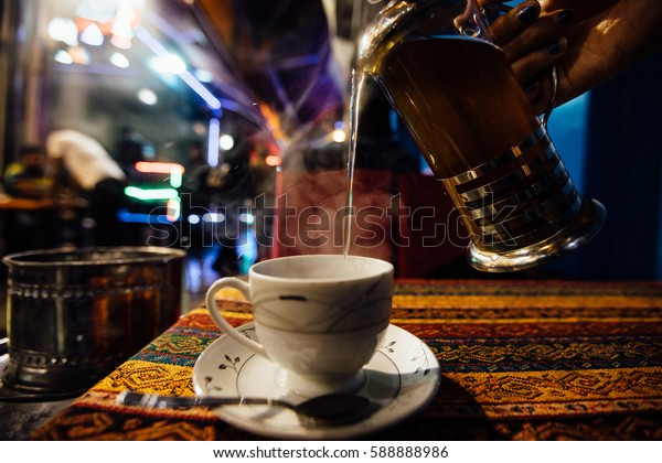Pour tea into a cup at an Street cafe. Jets of steam. Arabic flavor.
