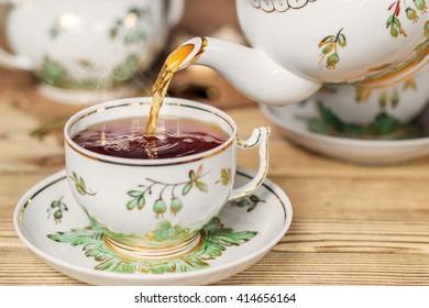 Pour tea into a cup. Vintage kitchen utensils. Shallow DOF